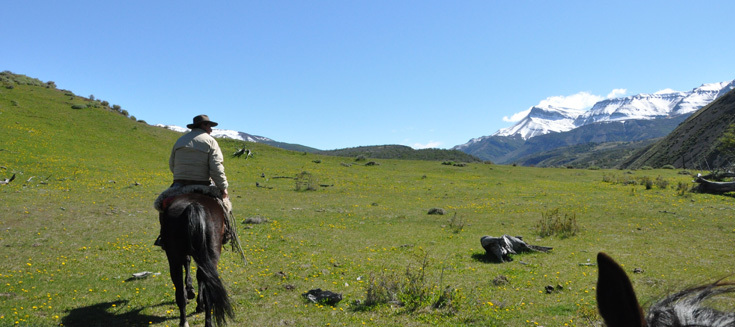 A gaucho leads a group on horseback. The Paine Massif is seen on the right.