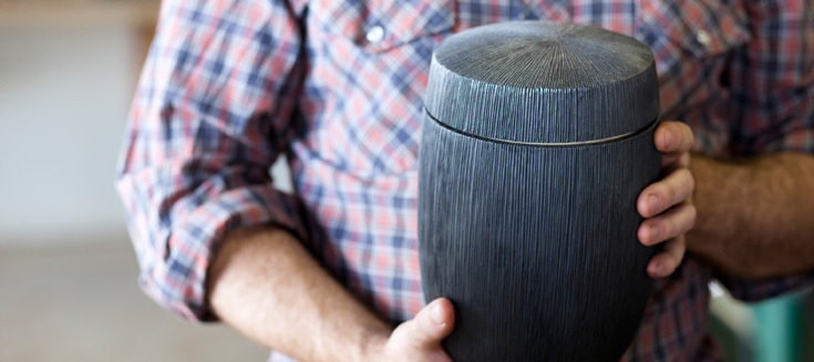 Joshua Vogel holding one of his vessels coated in graphite.