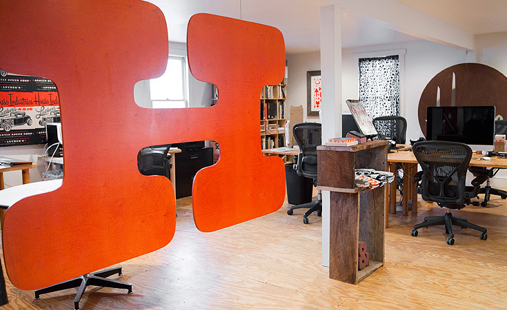 A giant H hangs in the center of the studio in House Industries's trademark orange.