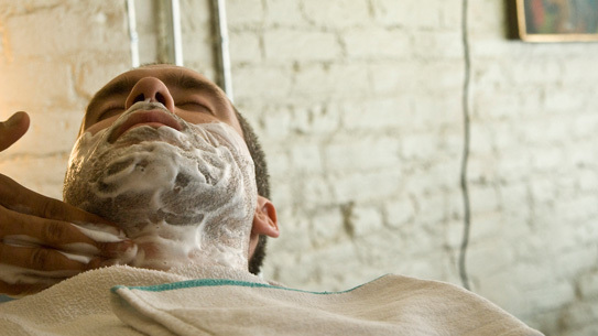 A customer is prepped for a straight razor shave.