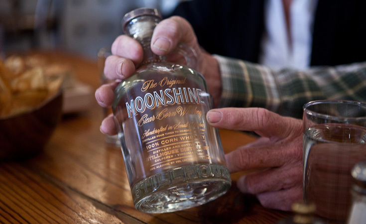 Chuck Miller with a bottle of Original Moonshine
