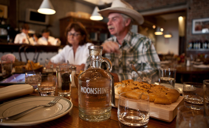 Chuck Miller with his wife Jeanette Miller and a bottle of Original Moonshine