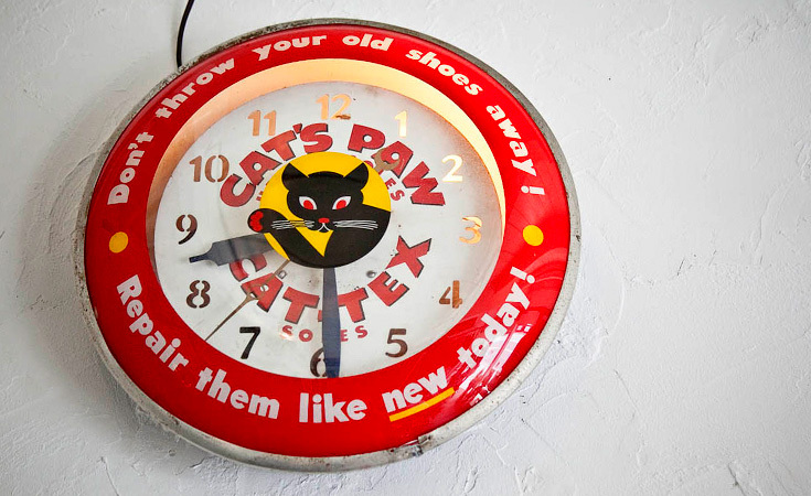 A Cat's Paw clock hangs from the wall.