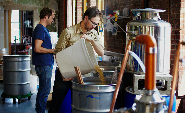 Matthew Million, factory manager with Rob Easter, distiller.  Easter is mixing the corn grains with boiling water.