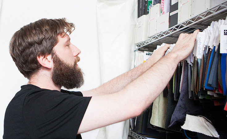 Technical and performance fabrics are an integral part of Outlier. Here Abe thumbs through their swatch library.